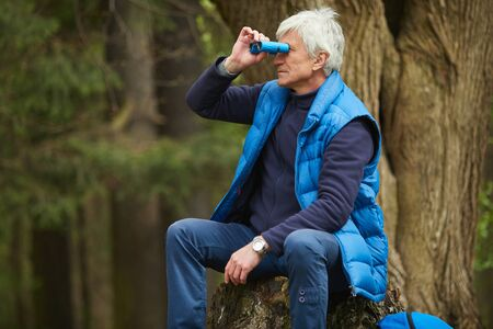 Portrait of active senior man looking in binoculars while sitting by tree during hike in autumn forest, copy space