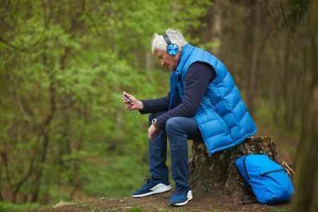 Side view portrait of active senior man listening to music via smartphone while sitting by tree and resting during hike in autumn forest, copy space