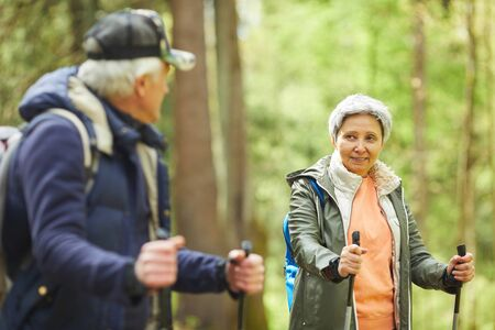 Waist up portrait of active senior woman enjoying Nordic walking during hike in forest with husband, copy space 스톡 콘텐츠