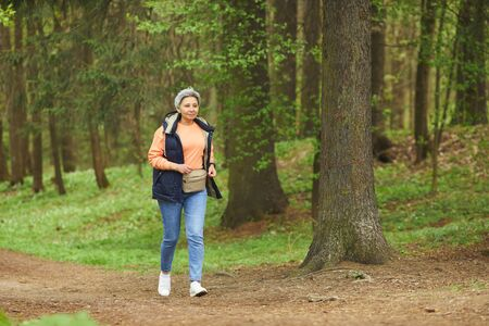 Full length portrait of active senior woman running while enjoying hike in beautiful autumn forest, copy space 스톡 콘텐츠