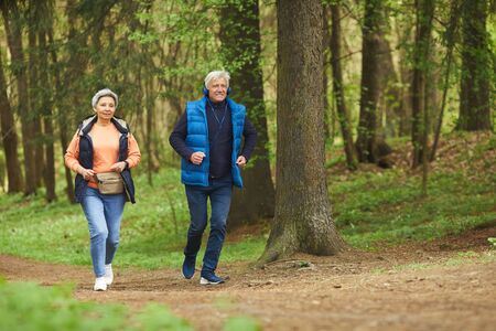 Full length portrait of active senior couple enjoying morning run in beautiful green forest, copy space
