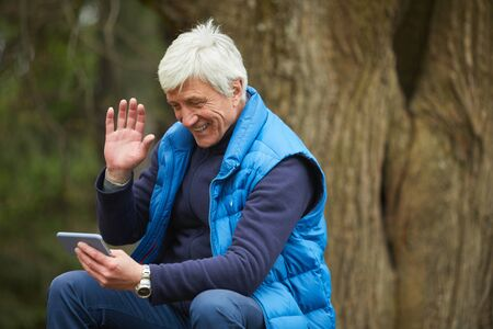 Portrait of active senior man smiling at smartphone and waving in video call during hike, copy space Banque d'images
