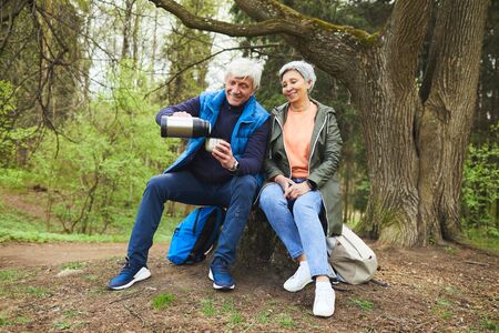 Full length portrait of cheerful senior couple enjoying hot tea from flask while resting during hike in autumn forest, copy space