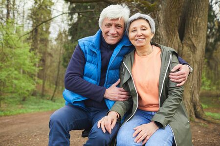 Portrait of active senior couple smiling happily looking at camera while posing during hike in autumn forest, copy space