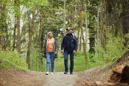 Full length portrait of active senior couple walking towards camera while enjoying hike in beautiful autumn forest, copy space