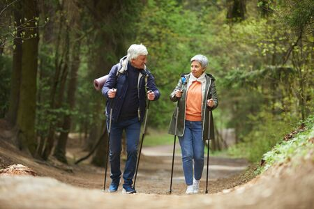 Full length portrait of active senior couple walking towards camera with Nordic poles while enjoying hike in beautiful autumn forest, copy space