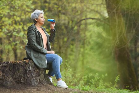 Side view portrait of active senior woman holding binoculars while enjoying hike in beautiful autumn forest, copy space