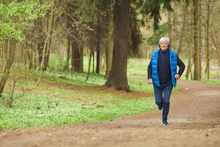 Wide angle portrait of active senior man listening to music while running in beautiful autumn forest, copy space