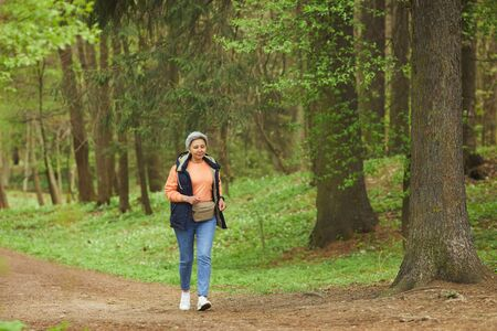 Wide angle portrait of active senior woman running during hike in beautiful autumn forest, copy space