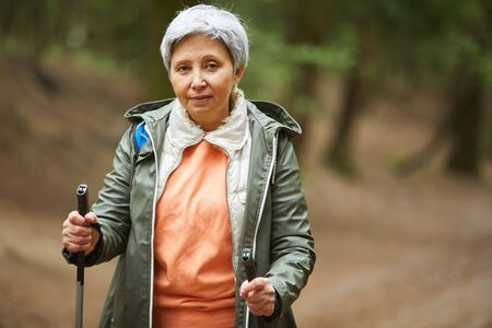 Waist up portrait of active senior woman looking at camera while enjoying Nordic walk during hike in autumn forest, copy space