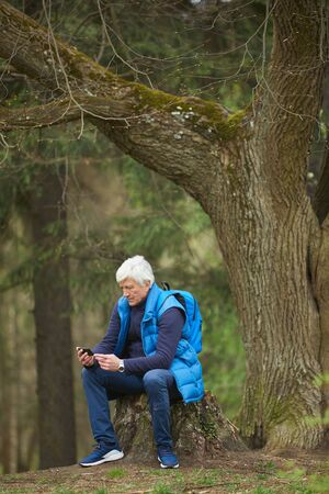 Vertical full length portrait of active senior man using smartphone while resting during hike in autumn forest, copy space above