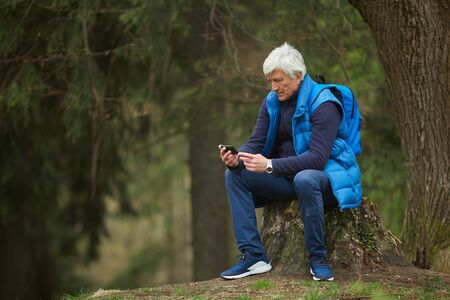Full length portrait of active senior man using smartphone while sitting on stump and resting during hike in autumn forest, copy space