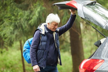Waist up portrait of modern senior man opening trunk of hatchback car while going on hike in forest, copy space