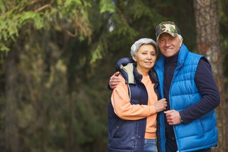 Waist up portrait of active senior couple embracing and looking at camera while enjoying hike in forest, copy space Banque d'images