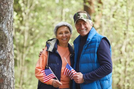 Waist up portrait of active senior couple holding USA flags and looking at camera while enjoying hike in forest, copy space
