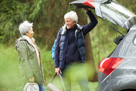 Waist up portrait of modern senior couple opening trunk of car and smiling happily while going on hike in forest, copy space Banque d'images