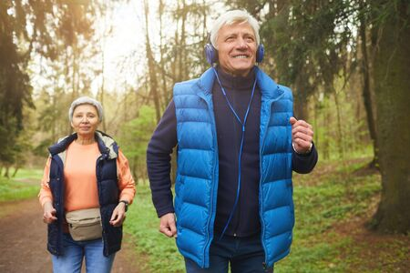 Front view portrait of active senior couple running in forest, focus on smiling man wearing headphones and enjoying music