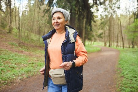 Waist up portrait of active mature woman running in forest or park and enjoying nature, copy space