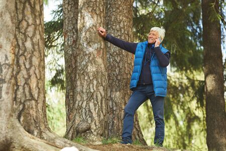 Full length portrait of modern senior man speaking by smartphone while leaning on tree in beautiful forest scene, copy space