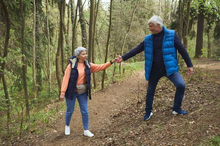 Full length portrait of active senior couple helping each other while climbing on hill during hike in forest, copy space