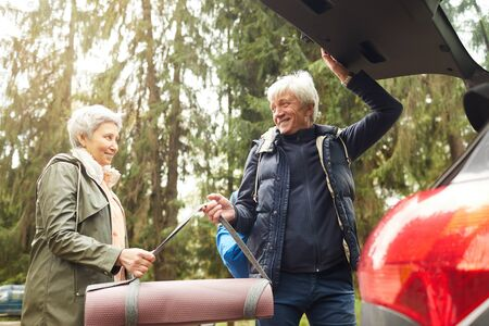 Low angle portrait of modern senior couple opening trunk of car and smiling happily while going on hike in forest