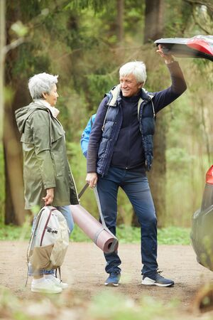 Full length portrait of modern senior couple opening trunk of car and smiling happily while going on hike in forest