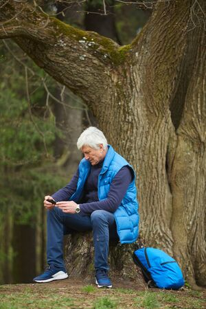 Vertical full length portrait of active senior man using smartphone while sitting by tree and resting during hike in autumn forest, copy space