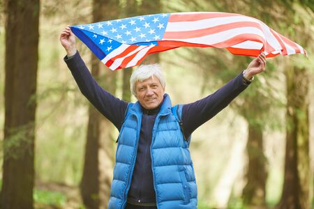 Waist up portrait of active senior man holding American flag and smiling at camera while enjoying hike in forest, copy space