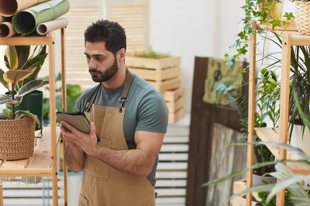 Waist up portrait of bearded man wearing apron using digital tablet while counting stock in flower store, copy space