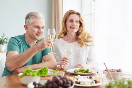 Portrait of loving mature couple raising champagne glasses while enjoying romantic dinner at home, copy space
