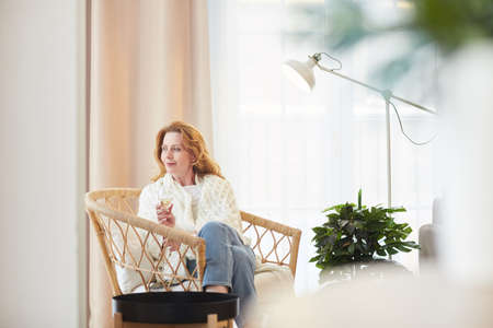 Wide angle portrait of elegant mature woman enjoying champagne while relaxing at home and looking away pensively, copy space Reklamní fotografie