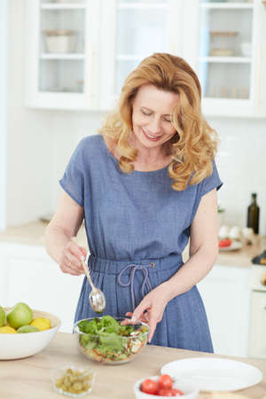 Vertical waist up portrait of elegant mature woman mixing salad in glass bowl while cooking in home kitchen, copy space