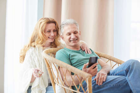 Warm-toned portrait of elegant mature couple looking at smartphone screen while relaxing together at home, copy space