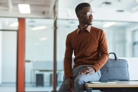 Portrait of young African-American man looking away while sitting on desk in modern office interior, copy space