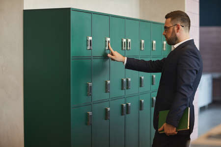 Portrait of mature bearded businessman opening locker in office or coworking, copy space