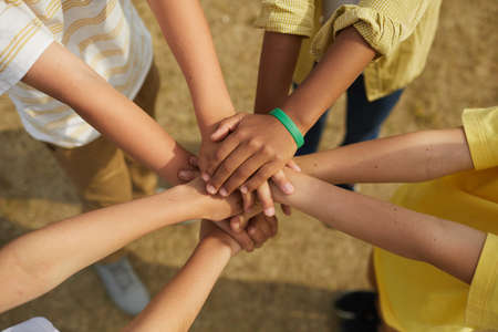 Top view close up at multi-ethnic group of children stacking hands while standing in circle outdoors, concept of friendship and unity