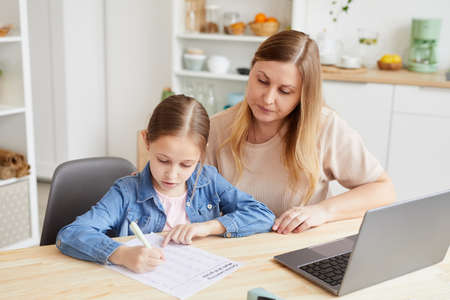 Portrait of caring adult woman helping girl doing homework or studying at home while sitting at desk in cozy interior, copy space