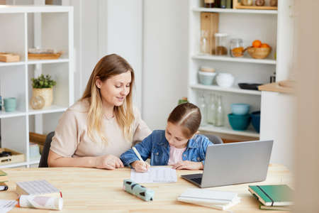 Portrait of smiling adult woman helping girl doing homework or studying at home in cozy interior, copy space