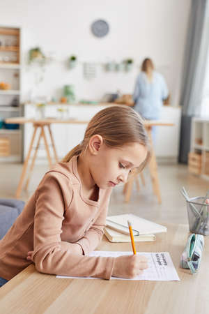 Vertical side view portrait of cute girl doing homework for elementary school while studying at home in cozy interior, copy space