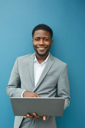 Vertical waist up portrait of contemporary African-American businessman holding laptop and smiling at camera while standing against blue wall in office, copy space above