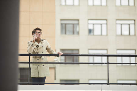 Wide angle portrait of elegant young businessman speaking by smartphone outdoors while leaning on railing and waiting in urban city setting, copy space