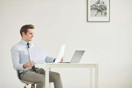Minimal side view portrait of smiling young businessman sitting at desk and working in office against white wall, copy space