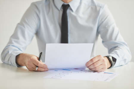 Minimal cropped portrait of unrecognizable young businessman holding document and while working sitting at desk and in office against white wall, copy space