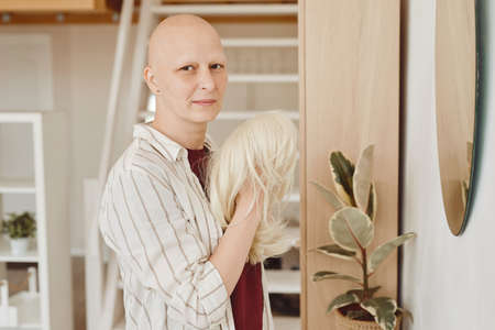 Warm-toned portrait of bald adult woman looking at camera holding wig while standing by mirror in modern home interior, alopecia and cancer awareness, copy space