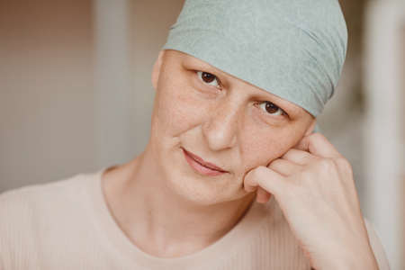 Warm-toned head and shoulders portrait of mature bald woman wearing headscarf and looking at camera pensively , alopecia and cancer awareness, copy space