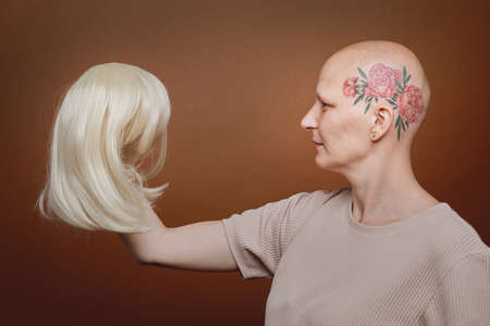 Side view portrait of confident bald woman holding wig of blonde hair against brown background in studio, alopecia and cancer awareness, copy space