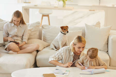 Warm-toned family scene of young mother helping little daughter draw or study with teenage girl and pet dog sitting on comfortable white couch in home interior, copy space Foto de archivo