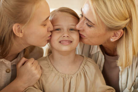 Warm-toned close up portrait of mother and sister kissing cute little girl on both cheeks, family bonds and generations concept Foto de archivo