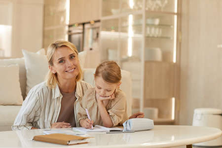 Warm-toned portrait of happy young mother smiling at camera while helping cute little girl drawing on studying at home, copy space