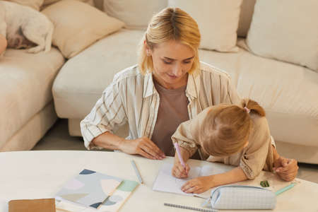 Warm-toned high angle portrait of happy young mother smiling while helping cute little girl drawing on studying at home, copy space